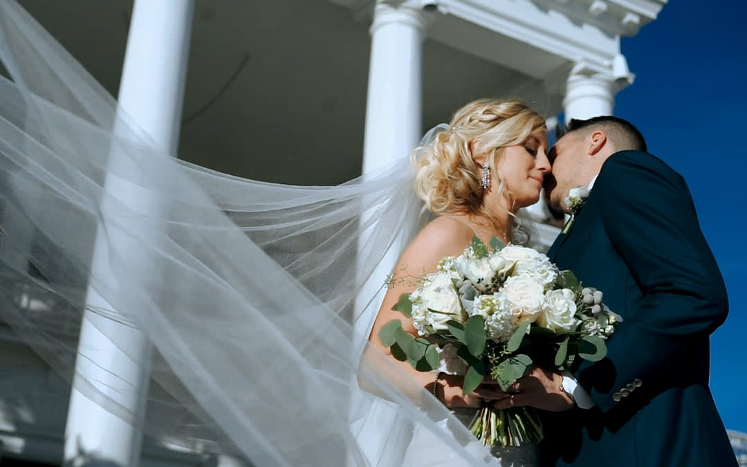 A bride and groom touch foreheads in front of the Manor House wedding venue in Littleton Colorado