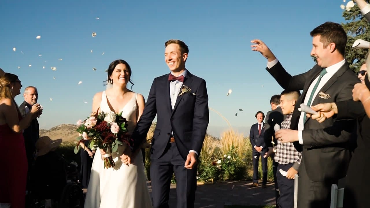 Colorado Wedding videographer Elizabeth Mae films a ceremony recessional where the guests are tossing flower petals at the Manor House wedding venue in Ken Caryl Colorado
