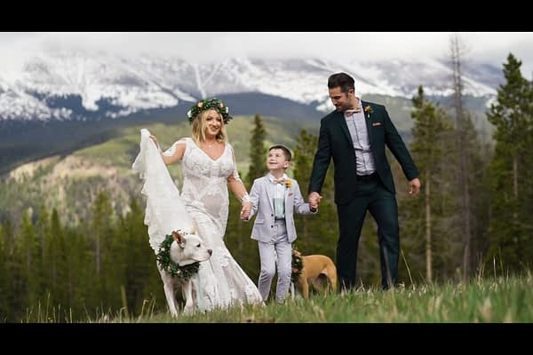 Bride and Groom walk on a hill surrounded by mountains with the groom's son and their two dogs by their side